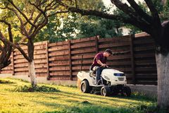 Homem que usa o trator do gramado para a grama de sega Ajardinar trabalha com ferramentas profissionais Fotografia de Stock Royalty Free