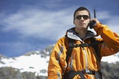 Homem que usa o Walkietalkie contra a montanha fotos de stock