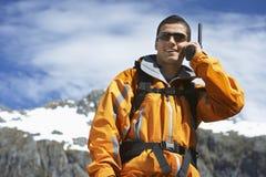 Homem que usa o Walkietalkie contra a montanha imagens de stock