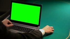Homem que usa serviços de aposta em linha no portátil, guardando a microplaqueta afortunada, tela verde video estoque