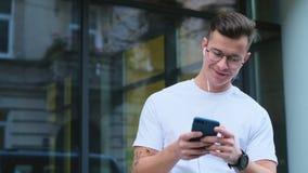 Homem que usa seus rolos através da alimentação social dos meios no dispositivo, sorrisos do smartphone das notícias em aplicaçõe filme