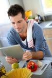 Homem que usa a tabuleta antes de cozinhar Fotografia de Stock Royalty Free
