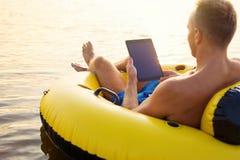 Homem que usa a tabuleta ao relaxar na ?gua fotografia de stock royalty free
