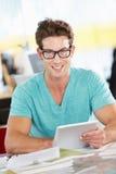 Homem que usa a tabuleta de Digitas no escritório criativo ocupado fotos de stock