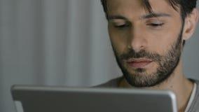 Homem que usa a tabuleta digital video estoque