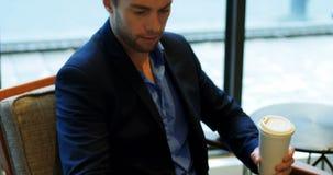 Homem que usa a tabuleta digital ao beber o café video estoque