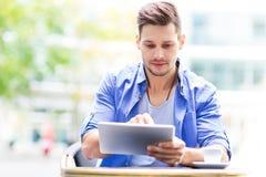 Homem que usa a tabuleta digital no café imagens de stock royalty free