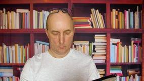 Homem que usa a tabuleta na biblioteca video estoque