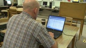 Homem que usa um computador em uma biblioteca video estoque