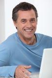 Homem que usa um computador portátil Fotografia de Stock