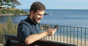Homem que usa um telefone esperto que senta-se em um banco video estoque