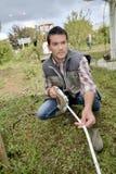 Homem que usa uma fita de medição no jardim Imagens de Stock