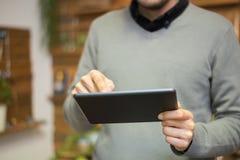 Homem que usa uma tabuleta digital Fotos de Stock