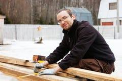 Homem que vê um handsaw do log Fotografia de Stock