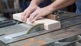 Homem que vê uma parte de madeira para um projeto de DIY fotos de stock