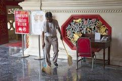 Homem que varre o assoalho altamente lustrado com escovas imagens de stock royalty free