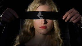 Homem que venda os olhos a mulher com fita preta, o conceito do amor cego e a submissão video estoque