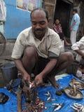 Homem que vende peixes em um mercado de rua Fotografia de Stock Royalty Free