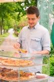 Homem que vende a pizza pela fatia foto de stock royalty free
