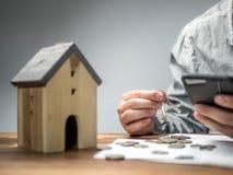 Homem que verifica contas do telefone esperto e que tem problemas financeiros com débito da casa, conceito do dinheiro , os bens  imagens de stock royalty free