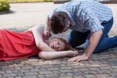 Homem que verifica o pulso da menina desmaiada Imagens de Stock