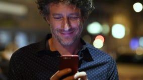 Homem que verifica o smartphone na noite vídeos de arquivo