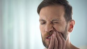 Homem que verifica os dentes na frente do espelho, doença dental, infecção da goma, pulpitis foto de stock royalty free