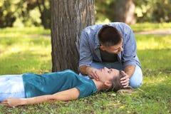 Homem que verifica para ver se há respirar da mulher inconsciente fotografia de stock