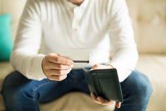 Homem que verifica seu cartão de crédito da carteira Imagem de Stock