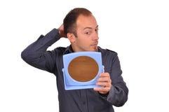 Homem que verifica sua queda de cabelo no espelho Fotografia de Stock Royalty Free