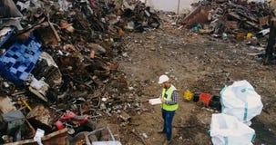 Homem que verifica a sucata no scrapyard 4k video estoque