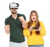 Homem que veste auriculares e mulher de VR com o controlador que joga jogos de vídeo fotografia de stock