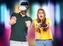Homem que veste auriculares e mulher de VR com o controlador que joga jogos de v?deo imagens de stock royalty free