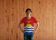 Homem que veste a camisa da cor da bandeira de Kiribati e que está com o akimbo no fundo de madeira da parede imagem de stock royalty free
