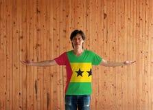 Homem que veste a camisa da cor da bandeira de Sao Tome and Principe e que está com os braços largamente abertos no fundo de made fotografia de stock