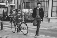 Homem que veste o terno elegante britânico na rua perto de um bycicle velho imagem de stock royalty free