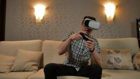 Homem que veste os auriculares da realidade virtual que jogam o jogo video estoque