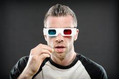 Homem que veste os vidros 3d que comem a pipoca Fotografia de Stock Royalty Free