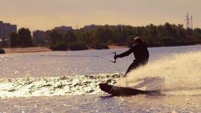 Homem que wakeboarding na água no por do sol Wakeboarder que faz truques filme