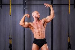 Homem rasgado calvo saudável novo com os músculos grandes que levantam no gym fotografia de stock