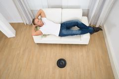 Homem relaxado com o aspirador de p30 robótico no assoalho Imagens de Stock