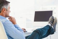 Homem relaxado com pés na mesa usando o computador Imagens de Stock Royalty Free