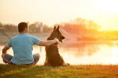 Homem relaxado e cão que apreciam o por do sol ou o nascer do sol do verão Imagens de Stock Royalty Free