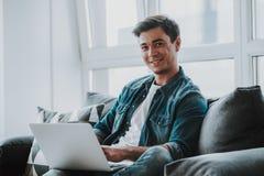 Homem relaxado que sorri ao sentar-se no sofá com portátil fotografia de stock royalty free