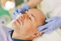 Homem relaxado que tem uma massagem de cara e um tratamento da casca fotos de stock royalty free