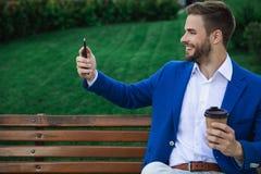 Homem relaxado que usa o telefone celular na natureza imagem de stock