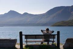 Homem Relaxed no banco do lago Foto de Stock