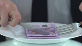 Homem rico que come cédulas com forquilha, conceito da sociedade de consumidor, pessoa ávida vídeos de arquivo