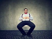 Homem robusto preguiçoso que senta-se na cadeira imagens de stock