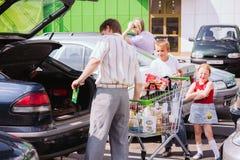Homem Rolls o carrinho de compras no estacionamento Fotografia de Stock